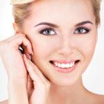 femme qui sourit pour montrer ses nouvelles dents grâce aux implants dentaires